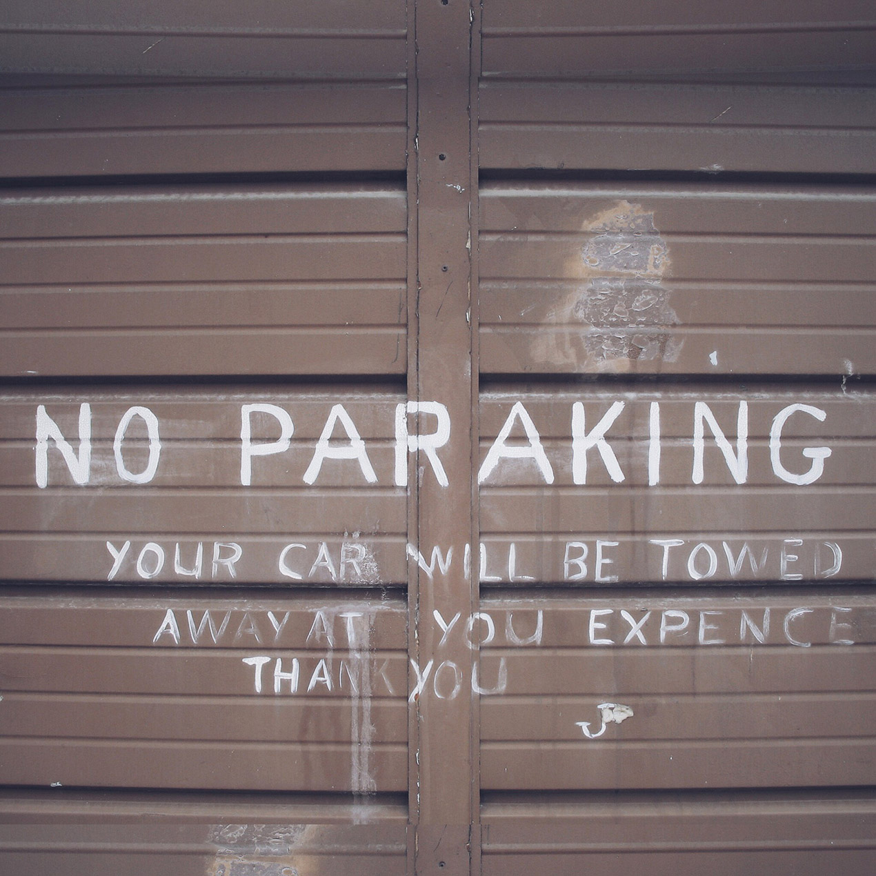 garage door with no parking spray painted in white