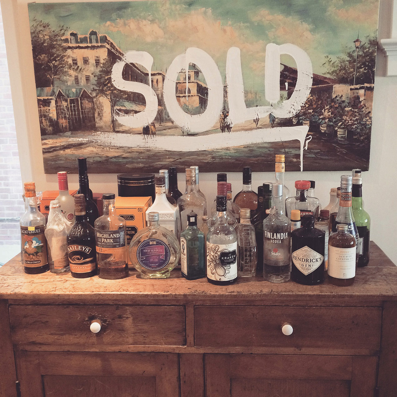 table full of alcohol and a painting behind it